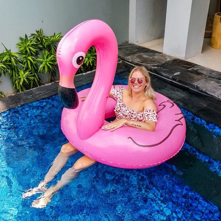 girl and pink flamingo floaty in pool