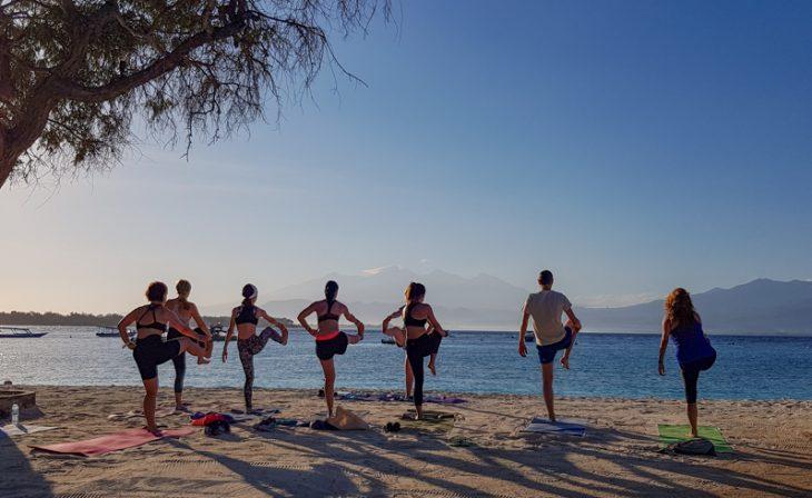 ihmiset joogaavat rivissa rannalla auringon noustessa