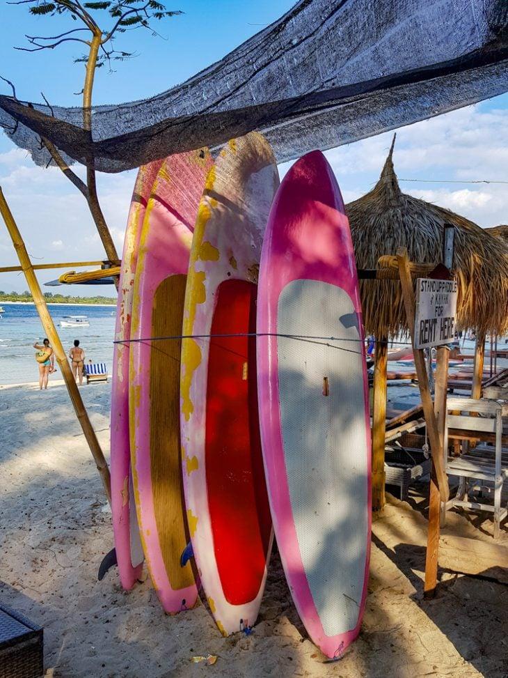 vaaleanpunaisia surffilautoja pystyssa rannalla