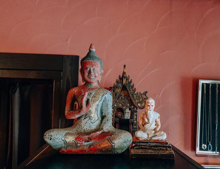 Kaksi buddha patsasta hyllyn päällä
