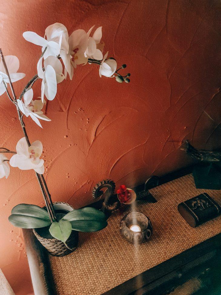 orkidea ja kynttilä lipaston päällä
