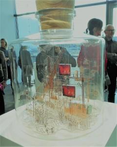Elektroniikan osista ja pienistä näytöistä lasiastiaan tehty kollaasi, pienoismaailma.