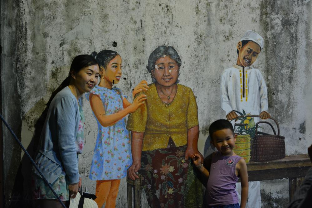 Aasialainen perhe maalattuna talon seinään